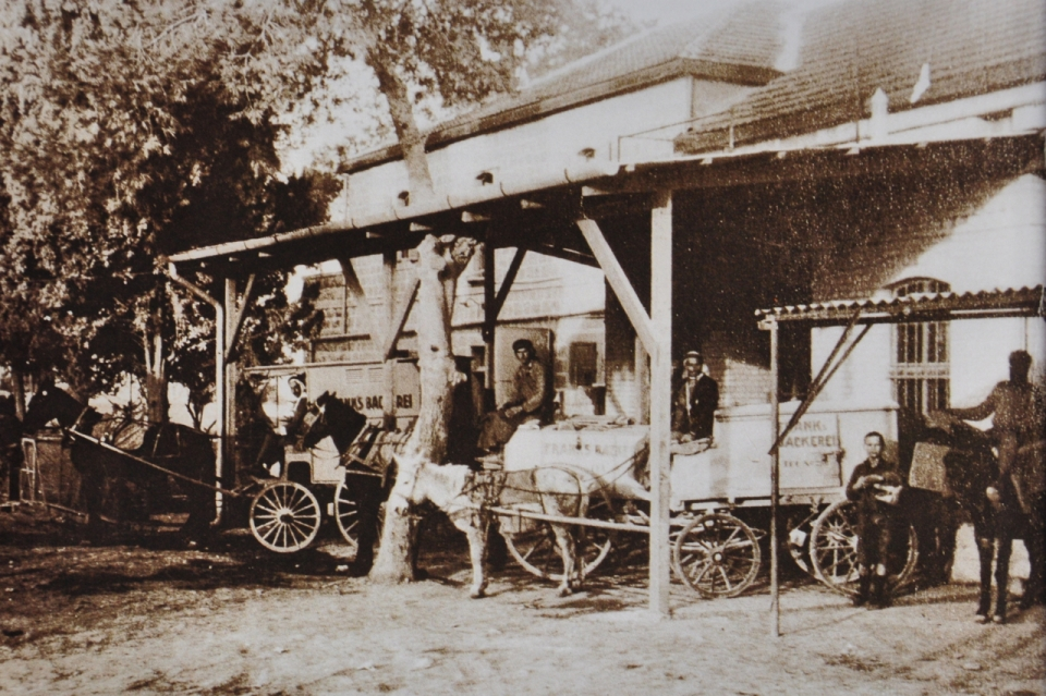early 20th century photo of courtyard of Frank Bakery behind the family residence, Arab wagoners and carts that delivered bread